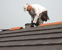Roofer placing new ridge tiles